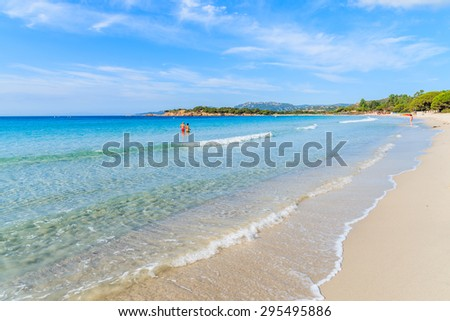 Unidentified couple of people walking in water on beautiful Palombaggia beach, Corsica island, France - stock photo