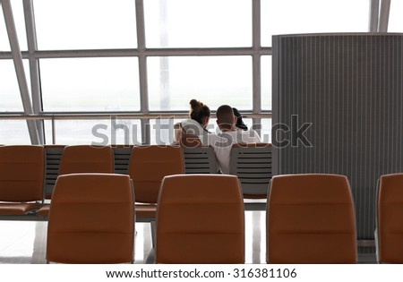 Unidentified Couple waiting at the international airport terminal - stock photo