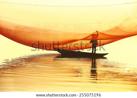 Unidentified fisher man check his nets in early morning on river in Hoian, Vietnam. Hoian is recognized as a World Heritage Site by UNESCO. - stock photo