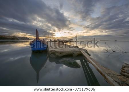 Unidentified fisherman boat at Jelutong Jetty, Penang, Malaysia during sunrise. - stock photo