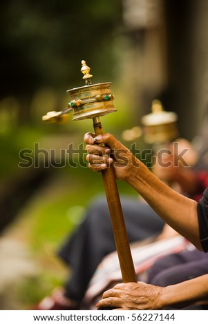Unidentified hands spinning a brass prayer wheel (mani) clockwise while reciting a mantra in the Tibetan Buddhist religion. Vertical copy space - stock photo