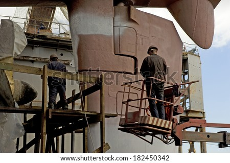 Unidentified men, the brigade painters paint the hull in dry dock city of Vladivostok  - stock photo