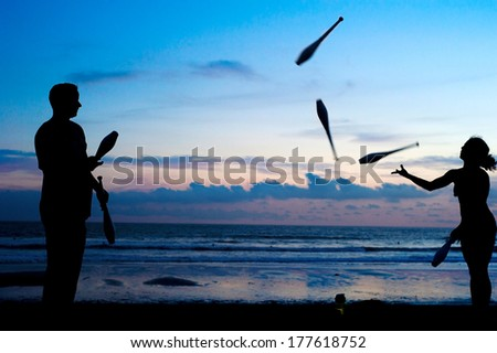 Unidentified people juggling on the ocean beach at sunset. Bali, Indonesi - stock photo