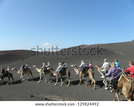 Unidentified people riding on camels in a line, through desert like volcanic landscape in Lanzarote. Timanfaya National Park - stock photo