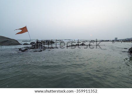 Unidentified pilgrims watch sunrise at Triveni Sangam as the sun rises near Vivekananda Rock Memorial and Thiruvalluvar Statue - stock photo