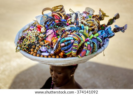 UNIDENTIFIED PLACE, SENEGAL - NOVEMBER 12, 2013: An unidentified woman carry souvenir basket on her had with african handcraft jewelry for sale - stock photo