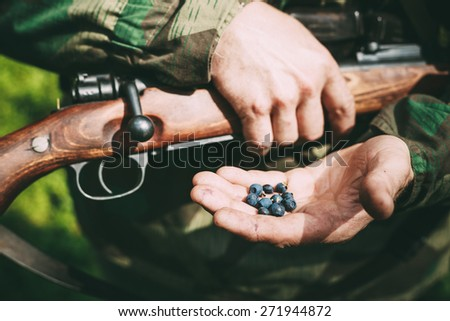Unidentified re-enactor dressed as German soldier holding holding a rifle and blackberries on hand. - stock photo