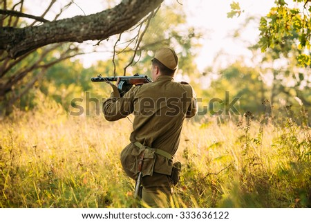 Unidentified re-enactor dressed as Soviet russian soldier aiming a machine gun at enemy - stock photo
