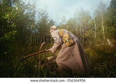 Unidentified re-enactor dressed as Soviet russian soldier running with rifle in forest grass - stock photo