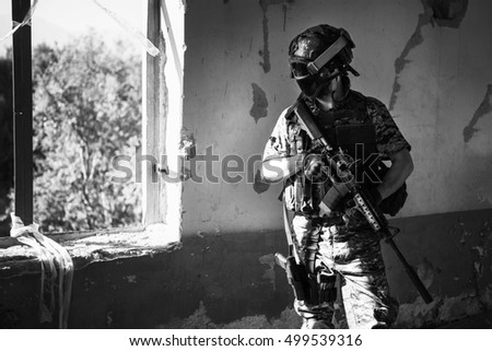 Unidentified soldier with mask aiming a rifle / Special forces soldier with rifle / Military, war, conflict, soldiers - Special forces soldier man hold Machine gun black and white