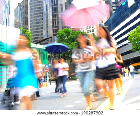 Unidentified women with umbrellas crossing the street in Singapore - stock photo