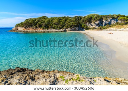 Unidentified young couple relaxing on beautiful Petit Sperone beach, Corsica island, France - stock photo