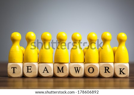 Unified pawn figurines, concept for success and achievement in business teams. Word teamwork with cube letters. - stock photo