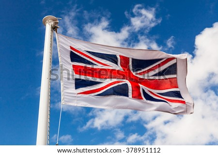 Union Jack Flag on a flag pole blowing in the wind. - stock photo