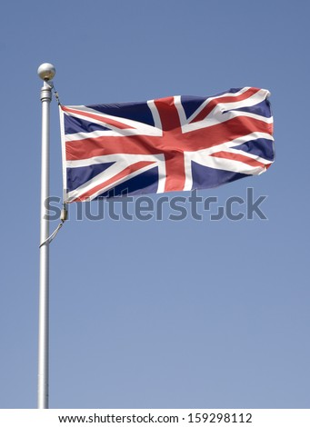 Union Jack in the breeze with a deep blue sky.