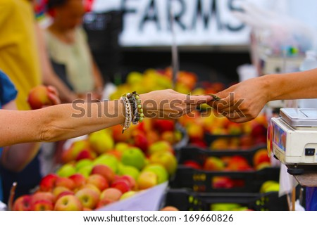 """Union Square Greenmarket, one of New York City's largest & best established direct markets for producers. Man's arm passing over bag of produce with """"FARMS"""" sign out of focus in the background - stock photo"""
