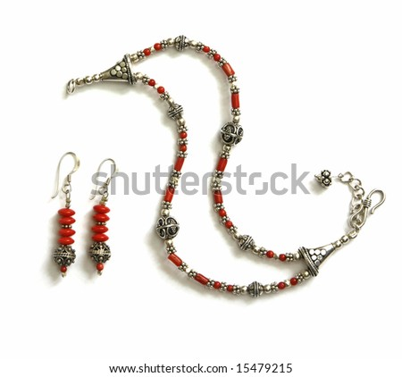 Unique bracelet with earrings made of silver and coral beads, isolated on white. Handicraft from Croatia. - stock photo