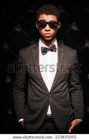 Unique modern style. Fashionable young Afro-American man wearing sunglasses and holding hands in the pockets while standing against dark background - stock photo