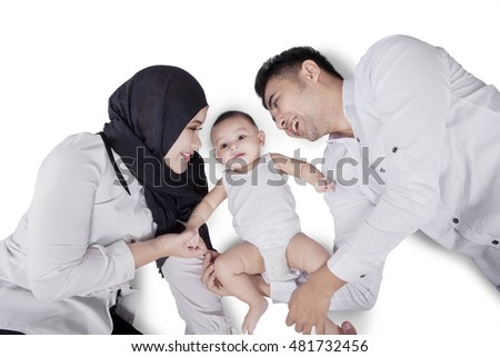 Unique perspective of a cute baby boy and his parents lying down on the floor in the studio