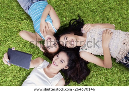 Unique perspective of beautiful teenage girls lying down on grass while taking self portrait with cellphone at field - stock photo