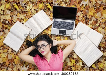 Unique perspective of pretty high school student smiling on the camera while lying on the autumn leaves with laptop and textbooks - stock photo