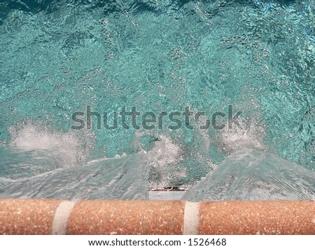 Unique perspective of waterfall into a swimming pool shot from directly above. The stone edge of the waterfall is at the bottom of the image, so the water is falling up into the image. Copy space. - stock photo