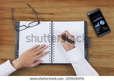 Unique Perspectives of entrepreneur hands writes business report on an agenda book - stock photo