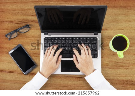 Unique Perspectives of Hands working on table with laptop computer, smart phone, and a cup of coffee - stock photo