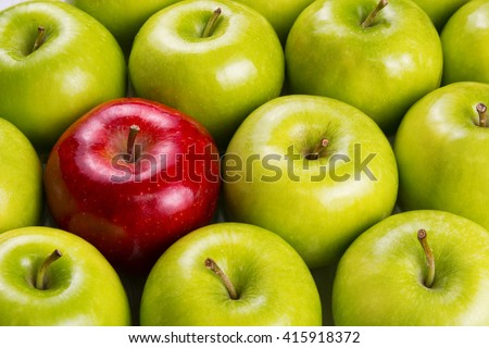 Unique Red Apple Among Group Of Green Apples
