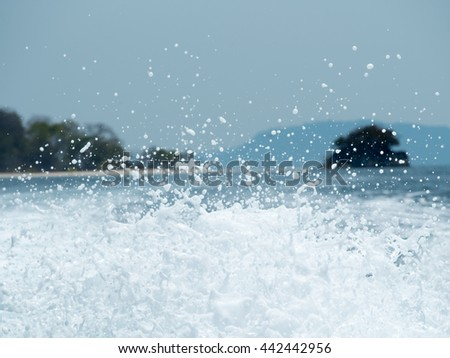 Unique sea water foam against sea and Island in background. Summer and travel concept. - stock photo