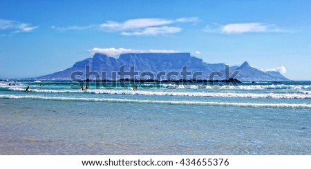 Unique Table Mountain on a background of blue sea, mountains and surfers in Cape Town. Beautiful South Africa. People enjoy vacation in Cape Town. Amazing ocean beach. Wonderful seascape. Blouberg - stock photo