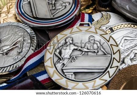 Unique vintage sport medals at flea market in Paris.  Billiards, swimming and ski medals. - stock photo