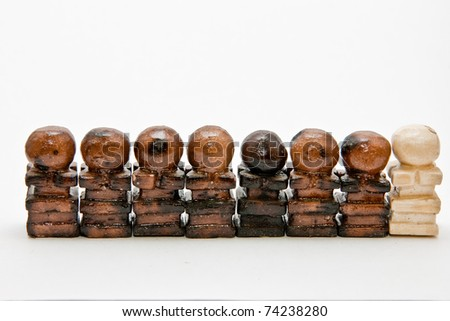 Unique white chalk handmade chess pawn piece in a row of black pawns. Eight pawns aligned. A trained white pawn to spy. Concept of intrusion and uniqueness - stock photo