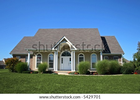 Uniquely designed suburban home with arches and porch. - stock photo