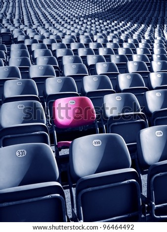 Uniqueness concept represented by red-pink colored stadium seat. There's no one like you! - stock photo