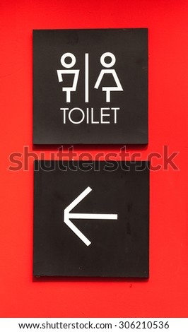 Unisex restroom or toilet and arrow sign on red wall style boutique . - stock photo