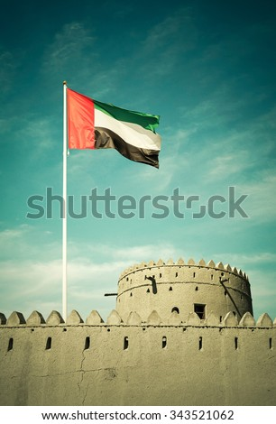 United Arab Emirates flag hoisted on an ancient burj. - stock photo