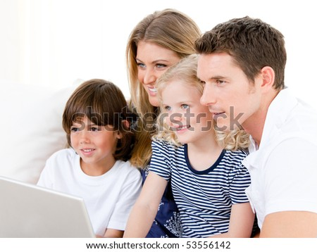 United family looking at the computer together at home - stock photo