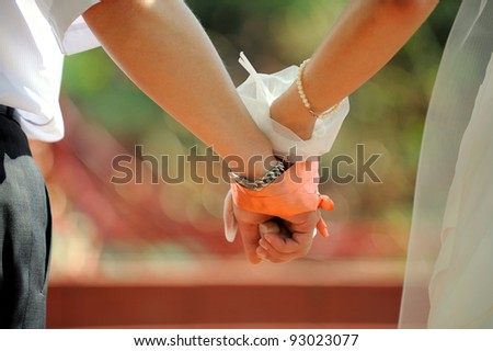 United hands of bride and groom by red ribbon - stock photo