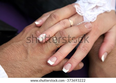 United hands of the bride and groom close up