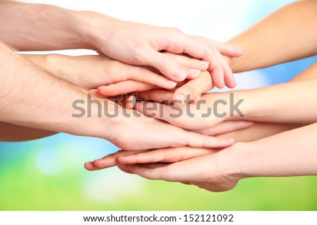 United hands on bright background. Conceptual photo of teamwork