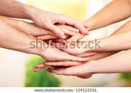 United hands on bright background. Conceptual photo of teamwork - stock photo