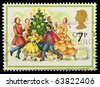 UNITED KINGDOM - CIRCA 1978: A British Used Christmas Postage Stamp showing Carol Singers around a Christmas Tree, circa 1978 - stock photo