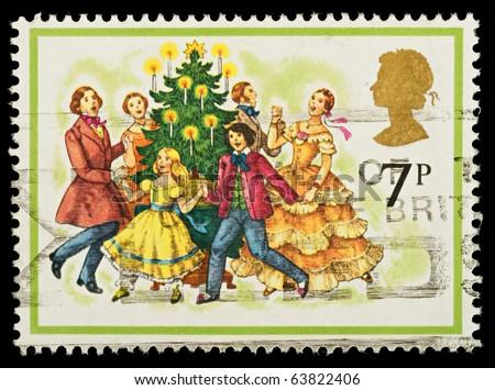 UNITED KINGDOM - CIRCA 1978: A British Used Christmas Postage Stamp showing Carol Singers around a Christmas Tree, circa 1978 - stock photo