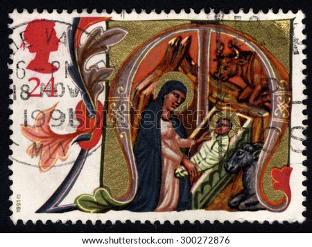 UNITED KINGDOM - CIRCA 1991: A stamp printed in the United Kingdom shows Christmas Mary placing Jesus in manger, circa 1991  - stock photo