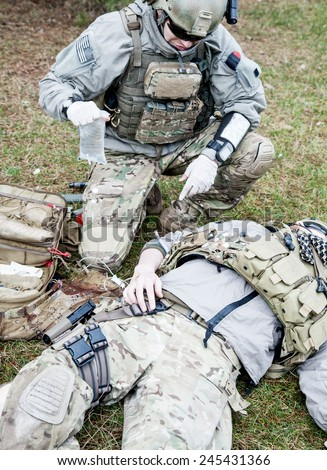 United States Army ranger treating the wounds of his injured fellow in arms - stock photo