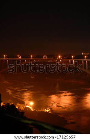 United States - Canada border bridge lit up at night by lights, at Niagara Falls - stock photo