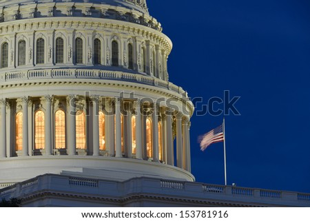 United States Capitol Building dome detail with flapping National Flag at night