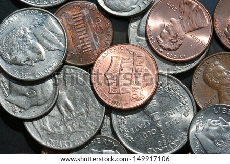 United States change (Penny, Nickel, Dime, & Quarter) scattered about on a black glass background. - stock photo
