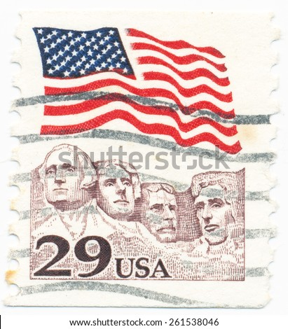 UNITED STATES - CIRCA 1991: A postage stamp printed in the United States, features waving US flag and Mount Rushmore National Memorial, circa 1991 - stock photo